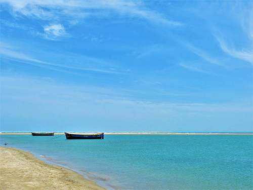 shoreline black boats on sea land