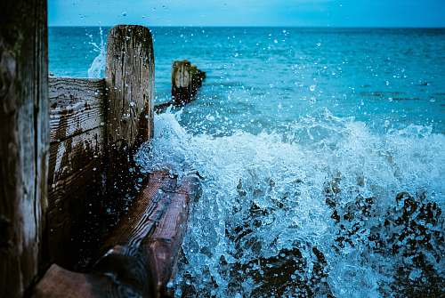 waves brown wooden dock with body of water during daytime ocean