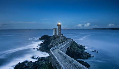 sea gray lighthouse on islet with concrete pathway at daytime coast