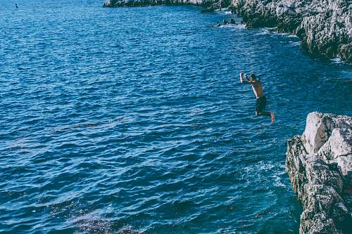 blue person jumped from rock cliff sport