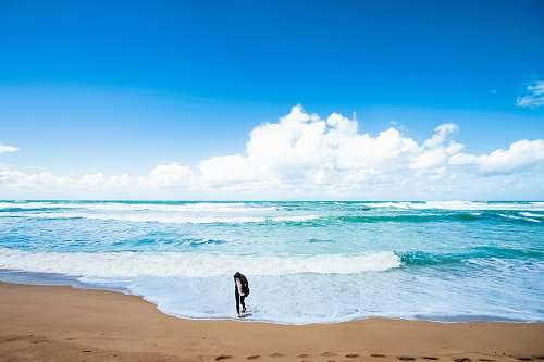 ocean person standing near shore beach