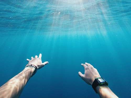 sea person wearing rectangular black watch blue