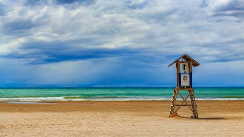 beach photo of lifeguard house on seashore during daytime sea