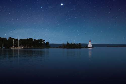 blue photograph of white lighthouse near calm body of water at night canada