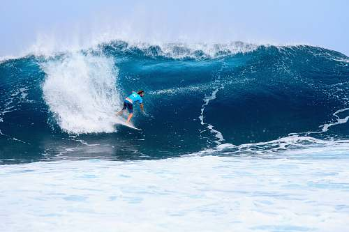 ocean surfer surfing on tidal wave sea