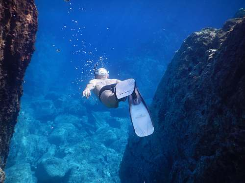 person underwater photo of person wearing flippers diver