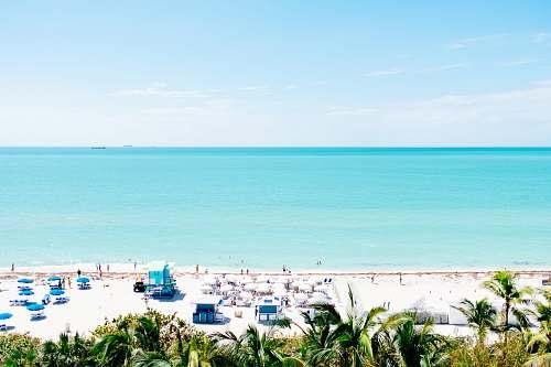 ocean white sand beach with stalls under blue sky sea