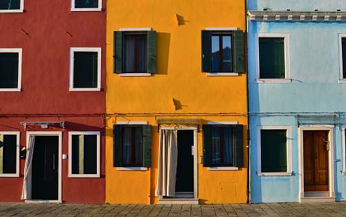 yellow minimalist photography of open doors and windows of colored buildings facade