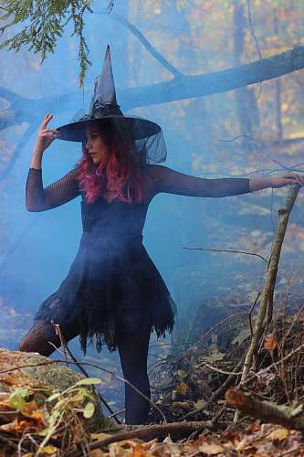 clothing woman in black witch costume standing beside rock person