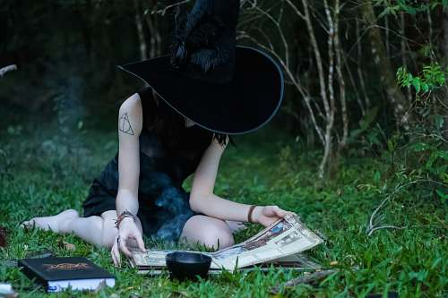 clothing woman reading book while sitting on green lawn grasses hat