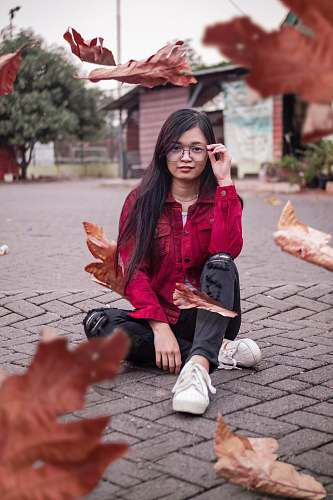clothing woman wearing red denim jacket and black skinny jeans sitting on concrete pavement holding eyeglasses footwear