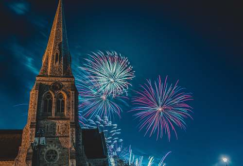 tower photo of pointed-edge church with fireworks architecture