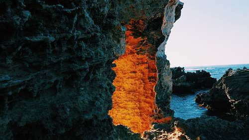 ocean lighted cave entrance near body of water sea