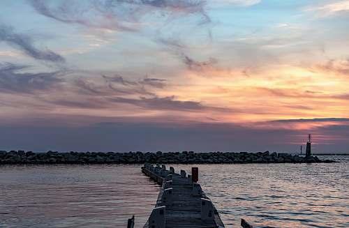pier brown wooden dock under gray and orange skies sea