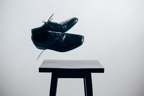 chair pair of black leather dress shoes over brown wooden table shoes