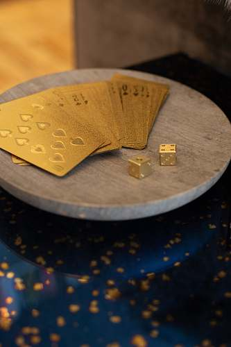 money gold cards and two dices on round wooden platform text