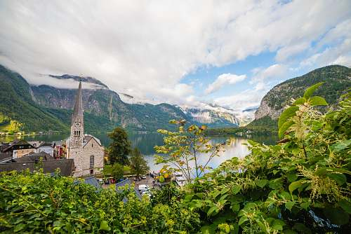 austria church beside body of water during daytime landscape