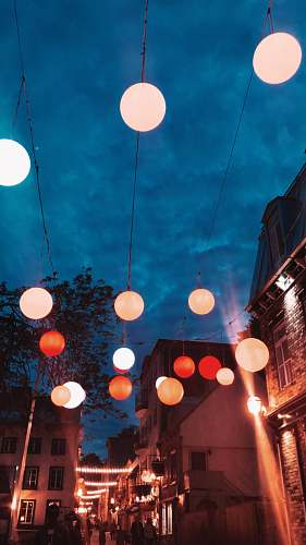 person lighted multicolored lanterns hanging over street lighting
