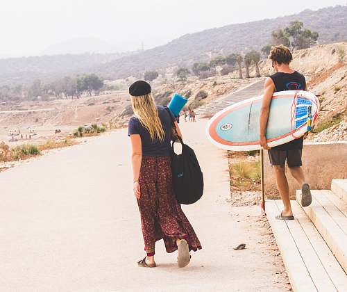 person man holding surfboard while walking with woman people