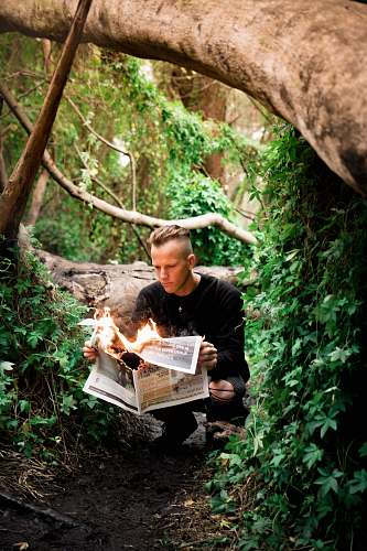 person man in black crew-neck sweater holding burning newspaper outdoors