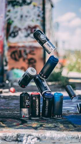 people selective focus photo of flying spray paint cans o person