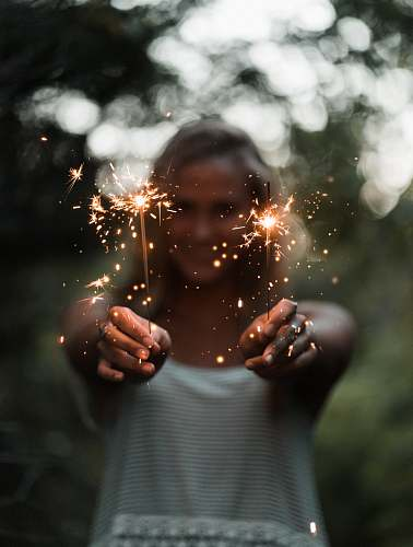 person selective focus photography of woman holding two sparklers people