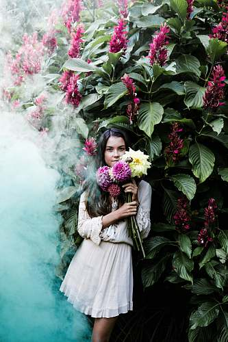 person woman holding yellow and purple flowers leaning back on green leafed plants with flowers people