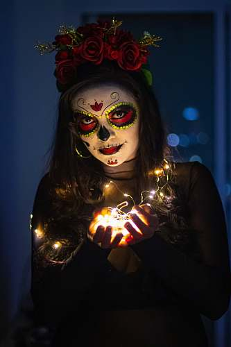 person woman with sugar skull paint face mask light