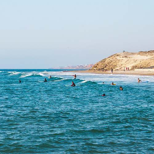 beach people riding surfboards in ocean at daytime water