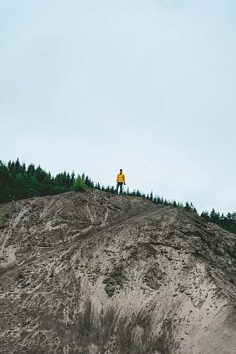 sweden person standing on rock formation near green trees blue