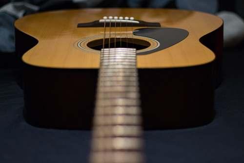 guitar tilt-shift photography of brown acoustic guitar electric guitar