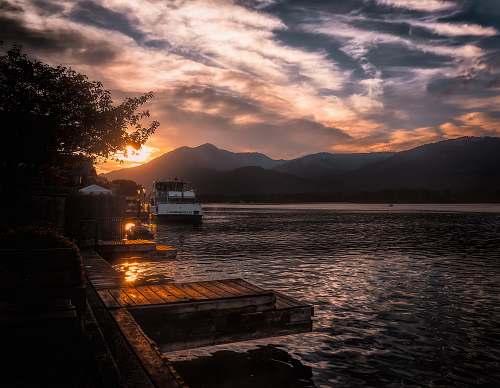 sunset boat on body of water near mountain austria