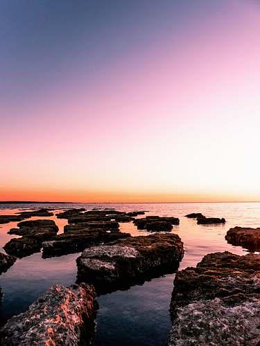 outdoors rocky island beside beach sunset