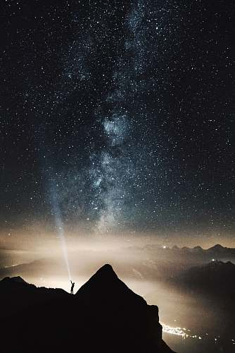 star silhouette of person on top of mountain pointing flashlight on sky filled with stars at night time milky way