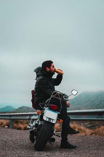 human man sitting on motorcycle while drinking beverage in can overlooking mountain under dark cloudy skies at daytime motorcycle