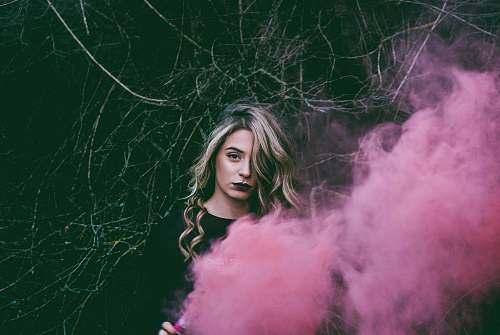 human woman standing near pink smoke person
