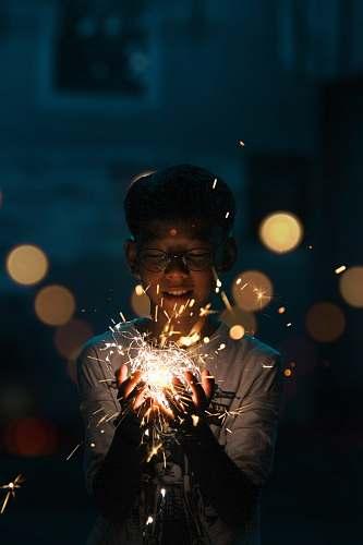 human boy holding lighting crackers lighting