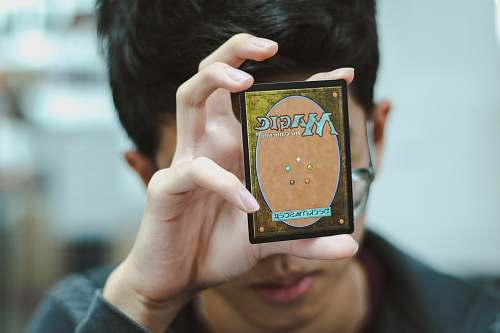 human boy holding Magic: The Gathering trading card people