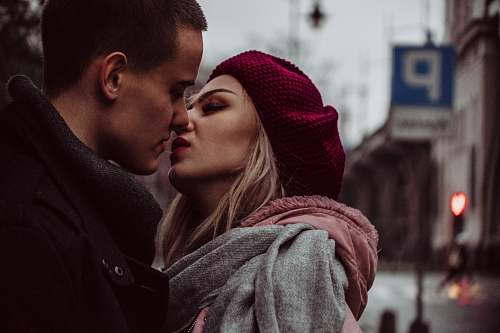 human man and woman standing while kissing beside street signage people