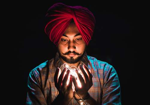 human man holding string lights people