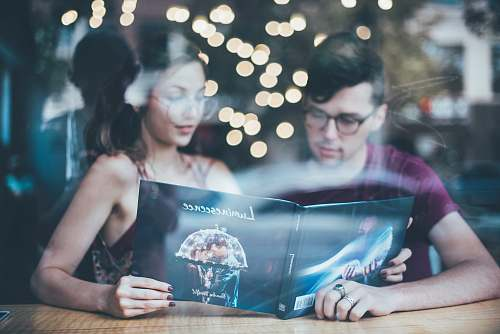 human man sitting beside woman while reading people