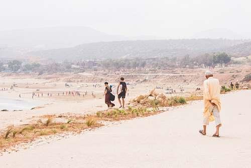 human man wearing brown coat walking on brown road people