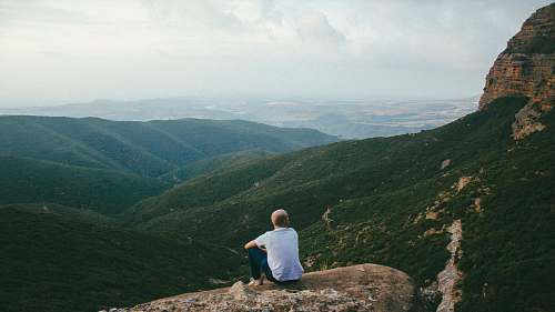 human person sitting on the edge of a cliff over looking mountains during daytime outdoors