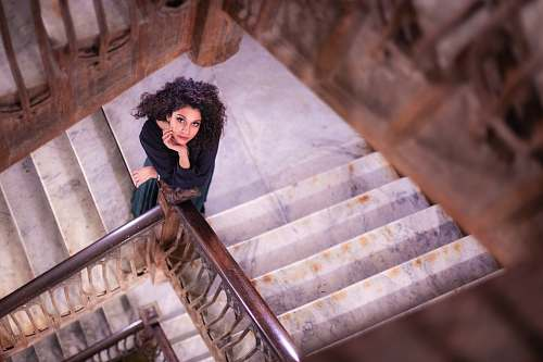handrail shallow focus photo of woman standing on stairs banister