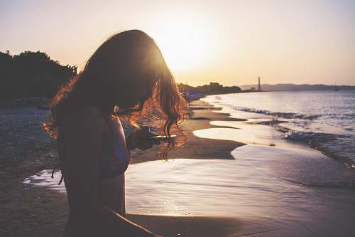 human silhouette photo of woman standing on seashore during golden hour people