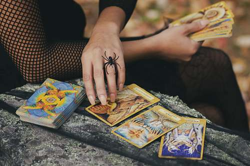 human woman holding tarot cards finger