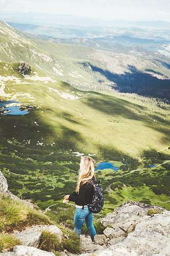 human woman standing on mountain during daytime outdoors