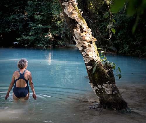 human woman wearing bikini near tree tree