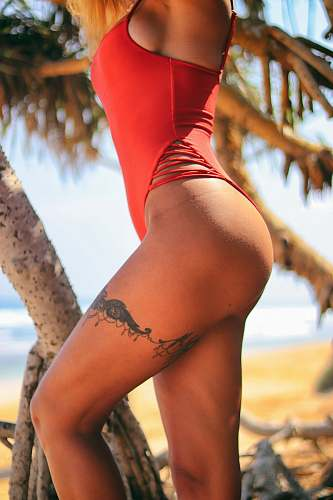 human woman wearing red bikini with floral thigh tattoo people