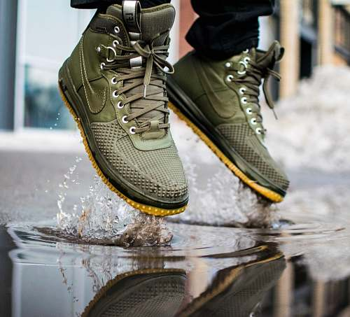 footwear person wearing green Nike sneakers jumping on water boot